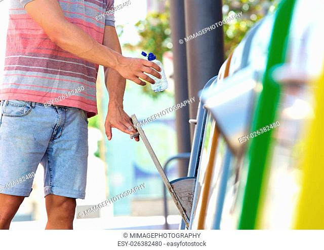 Man putting plastic bottle in recycling bin