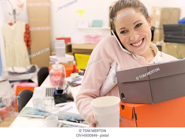 Smiling fashion buyer multitasking in office