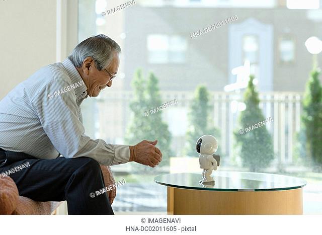 Senior man playing with robot
