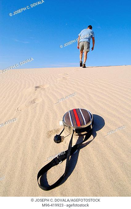 Slouching man walk up sand dune after throw away canteen. Mojave Desert. California. USA