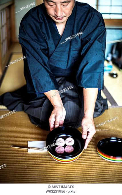Japanese man wearing traditional kimono knelling on floor, holding a bowl with Wagashi, sweets traditionally served during a Japanese Tea Ceremony