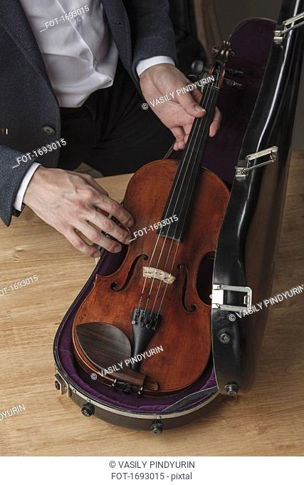 Midsection of man keeping violin in case at table