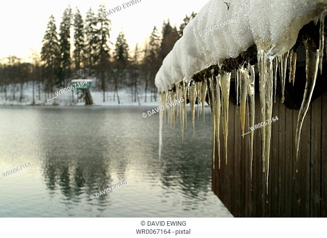 Icicles forming on the roof of a wooden boat shed, Lake Bled, Slovenia