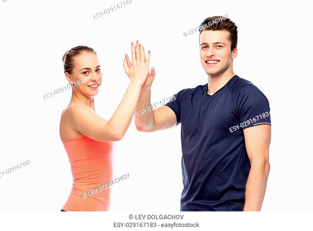 sport, fitness, gesture, lifestyle and people concept - smiling man and woman making high give