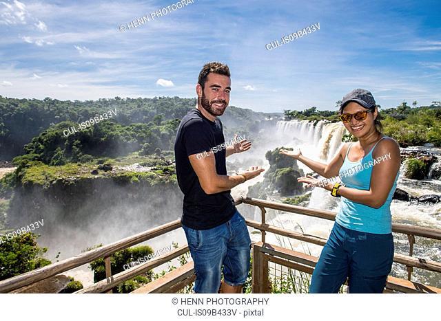Couple posing in front of Iguazu falls, Misiones, Argentina