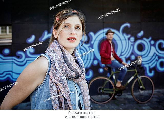 Germany, Hamburg, St. Pauli, Young woman and man on bicycle standing in front of graffiti