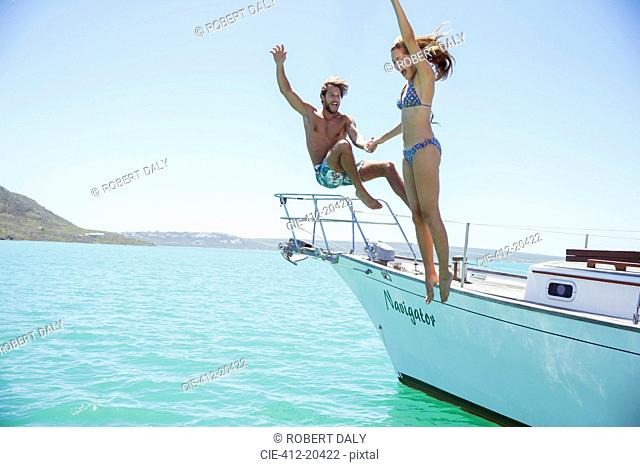 Couple jumping off boat together