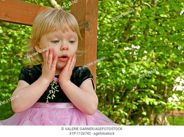 This stock image shows a two year old toddler girl outdoors in a pink princess dress with a surprised expression on her face Her little hands are on her cheeks...