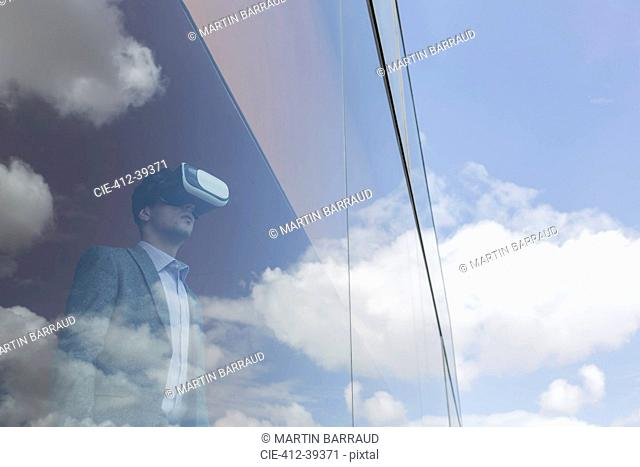 Businessman using virtual reality simulator at modern office window overlooking blue sky and clouds
