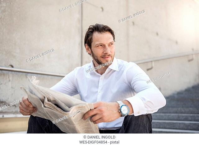Smiling businessman sitting on stairs reading newspaper