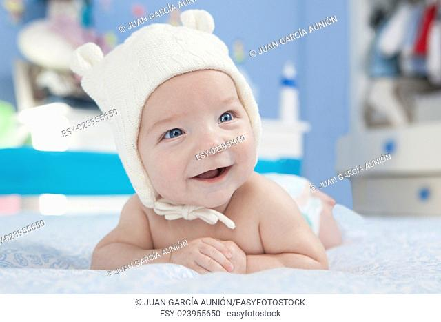 Portrait of a four months old baby smiling. He is faced down