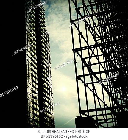 Foreground silhouette of the metal structure of a building and a residential building in South Dock, Docklands, London, England, UK, Europe