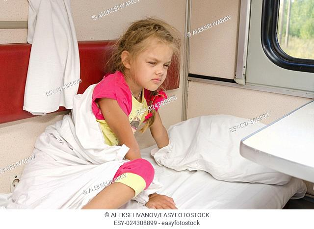 The girl on the train sleepily gets out of bed on the lower place in the second-class compartment wagon