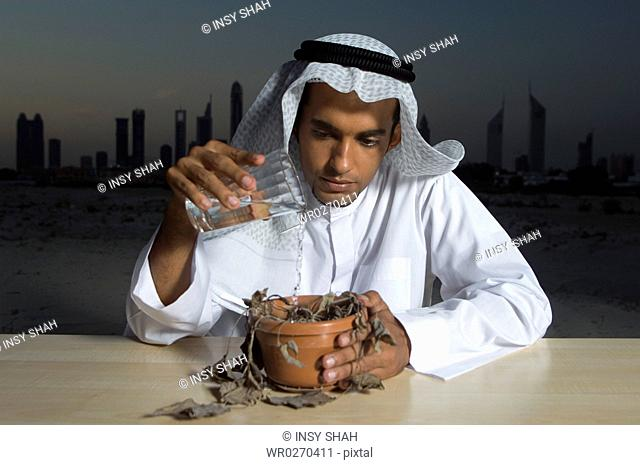 Young Arab man sitting at a desk with Dubai City in the background pouring water to a dead plant