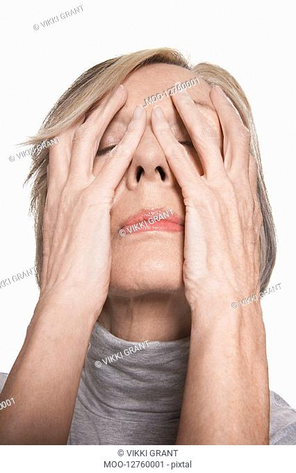 Senior woman with hands on face close-up