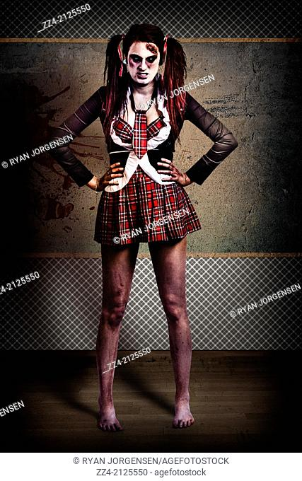 Crazy female zombie school student wearing not-so freshman uniform standing inside classroom in hostile akimbo pose in front of grunge chalkboard giving...