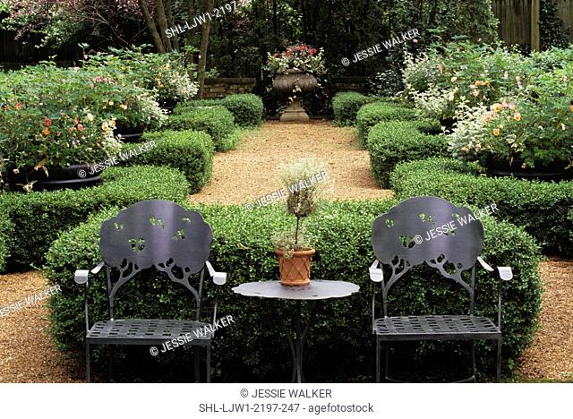 Garden: View from patio towards formal garden with boxed hedges. Metal patio furniture facing camera
