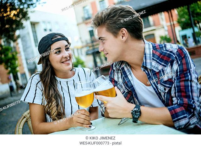 Young couple drinking beer at sidewalk cafe