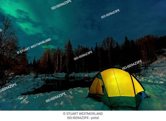 Aurora borealis, Northern Lights above tent lit up with lantern, near Chena Resort, near Fairbanks, Alaska