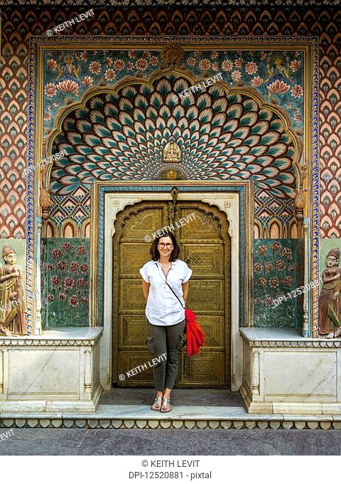 A female tourist stands in front of the Peacock Gate, City Palace; Jaipur, Rajasthan, India