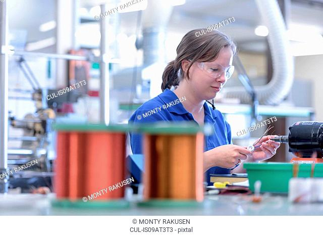 Female worker assembling electromagnetic coils in electronics factory