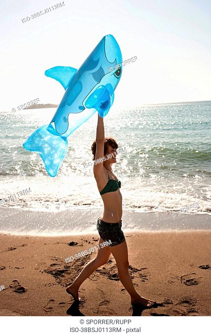 Woman with inflatable toy on beach