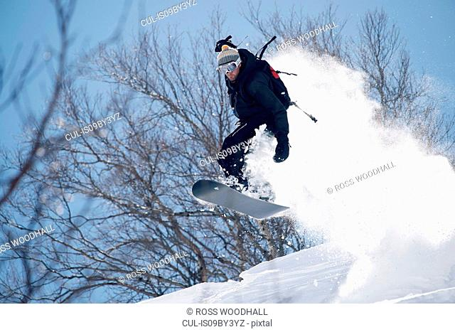 Male snowboarder snowboarding mid air on mountainside, Alpe-d'Huez, Rhone-Alpes, France