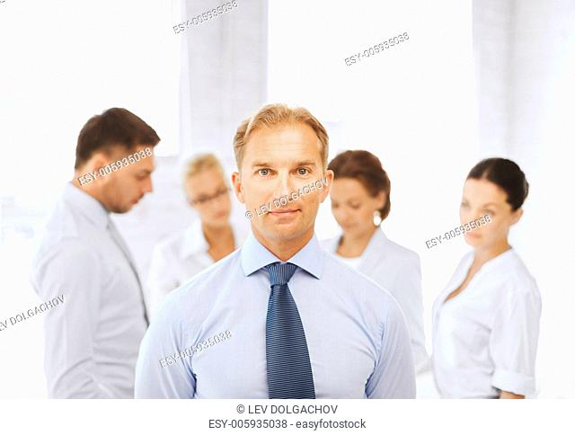 business, office, school and education concept - smiling handsome businessman with team on the back