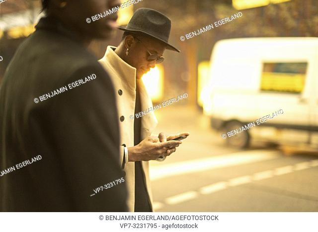 man using phone at street while walking next to friend, in Munich, Germany