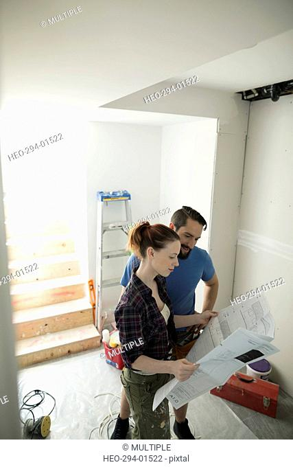 Couple reviewing blueprint for home improvement project