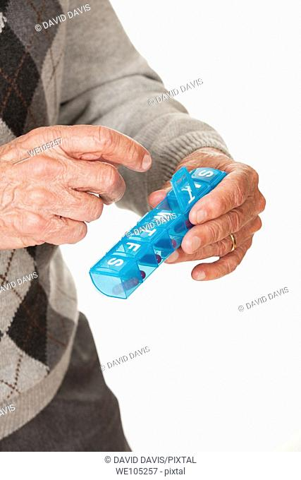 A Caucasian man getting his medicine out of a pill box on a white background