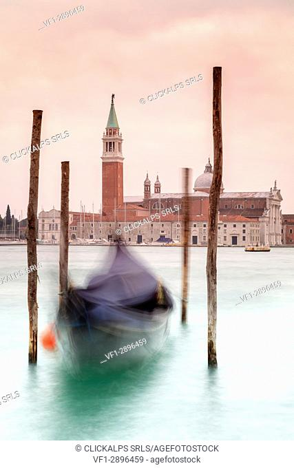Europe, Italy, Veneto, Venice. Gondolas tied up to wooden poles on the Canal Grande, in the background the monastery of San Giorgio Maggiore