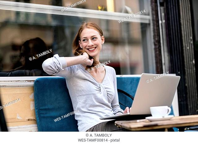 Smiling redheaded woman with laptop at sidewalk cafe
