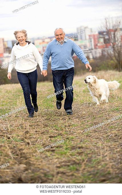 Smiling senior couple running hand in hand