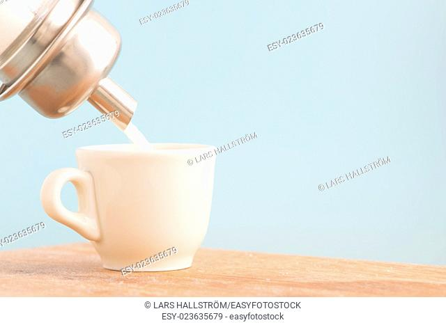Sugar dispenser pouring into white cup. Conceptual image of using too much sweetener and unhealthy eating and drinking