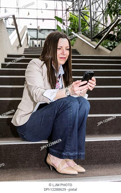 Mature business woman sitting on stairway in the atrium of an office building and texting on her smart phone; Edmonton, Alberta, Canada