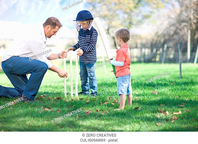 Father and sons preparing stumps for cricket