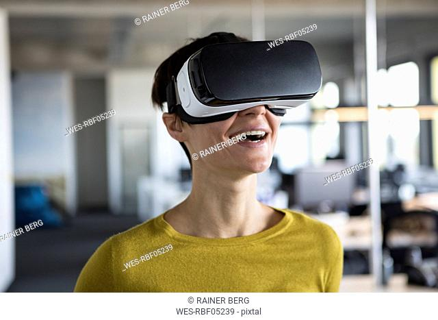 Happy woman in office wearing virtual reality glasses