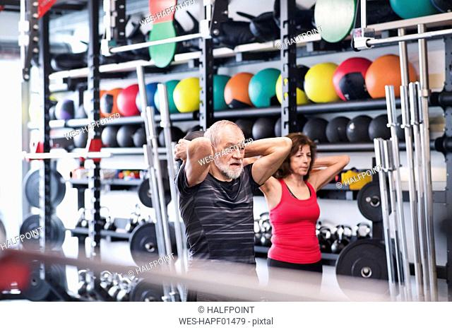 Senior mand and woman in gym exercising with medicine balls