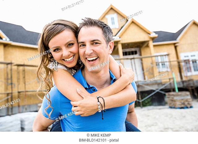 Caucasian couple hugging near house under construction