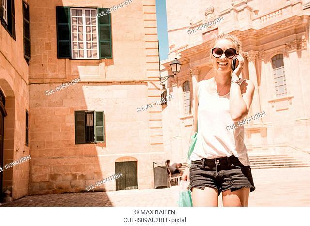 female tourist talking on smartphone in Ciutadella, Menorca, Spain