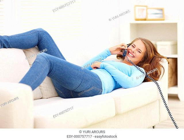 Cute young teen lying on a couch enjoying a conversation on the phone while at home