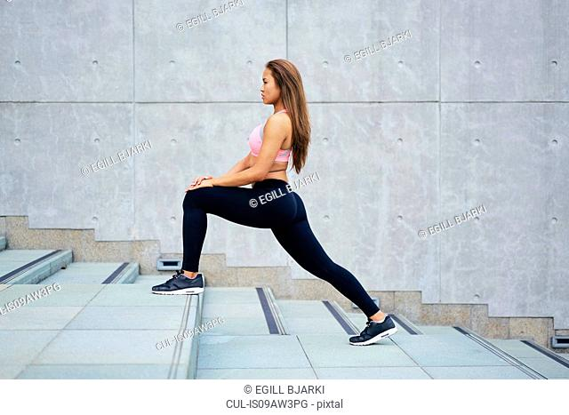 Young woman exercising stretching legs on city stairway