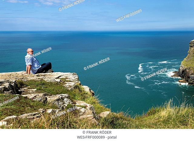 United Kingdom, England, Cornwall, Tintagel, Tourist sitting at cliff coast