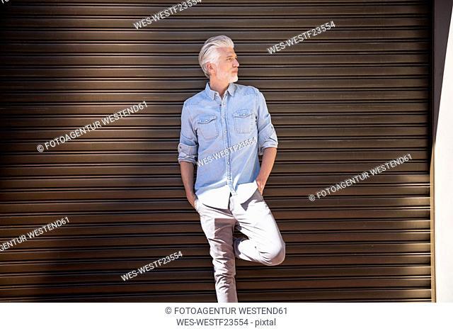 Mature man standing in front of roller shutter