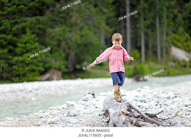 Young boy balancing on log next to stream