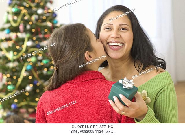 Daughter kissing mother in front of Christmas tree