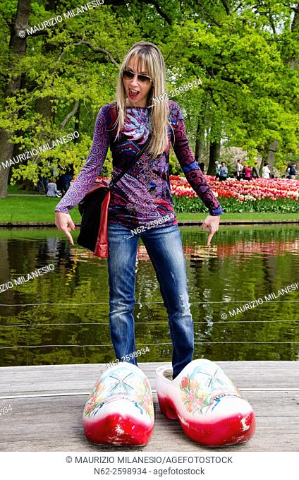 Woman amused indicates hooves giant who is wearing at park Keukenhof Amsterdam Netherlands