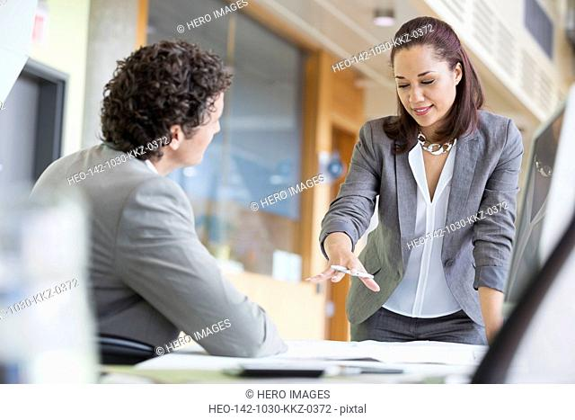 Businesswoman gesturing while reviewing blueprint with colleague