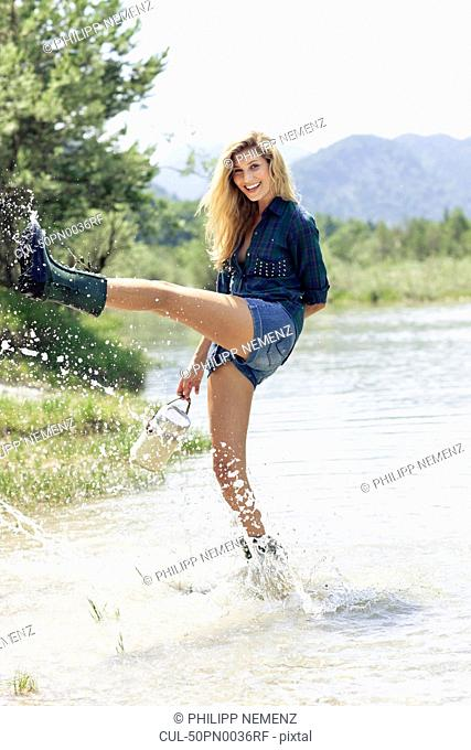 Woman in boots playing in river